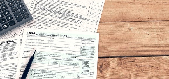 Tax forms with calculator and pen, spread out on a wooden surface.