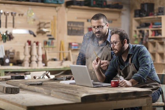 Two men in front of a computer in a workshop.
