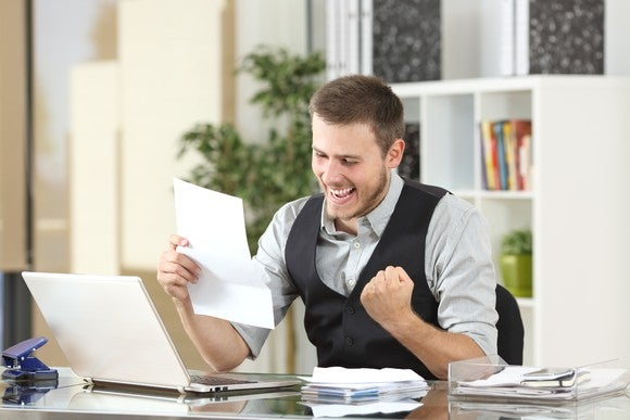 A seated man looking at a sheet of paper and clenching his fist in excitement