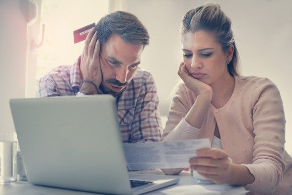 Couple sitting in front of a laptop as they look at a statement, worried