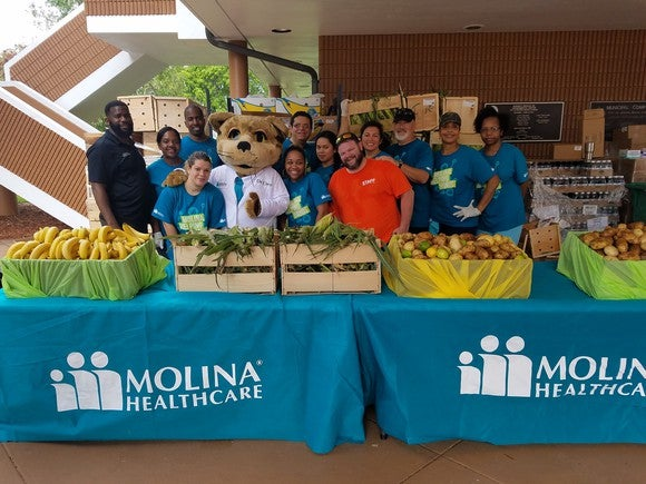 Volunteers with fruits and vegetables at tables featuring Moline Healthcare's logo.