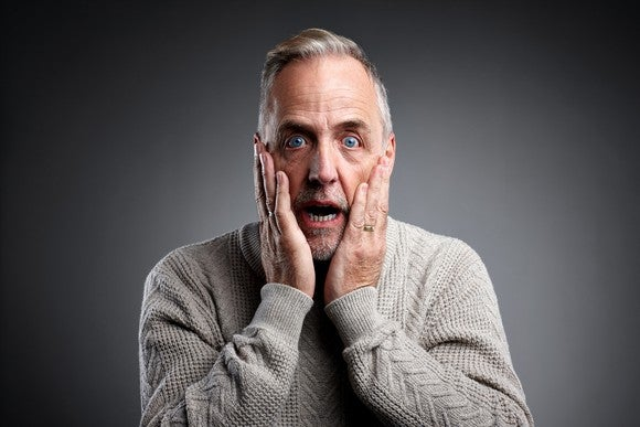surprised older man with mouth open and hands on cheeks