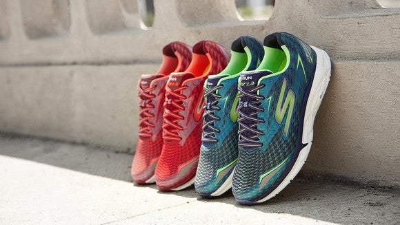 Two pairs of Skechers Go Run sneakers (one green and one red) propped up on a wall in the sun.