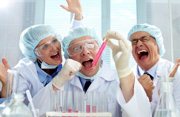 Three scientists, mouths agape, in a laboratory looking at a test tube filled with pink liquid and celebrating.