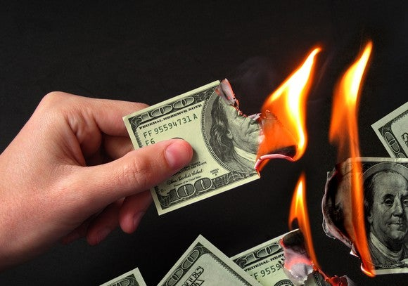 Hand holding a burning $100 bill with other bills burning in the background.