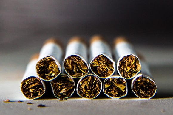 Nine cigarettes arranged in two rows on a flat surface.
