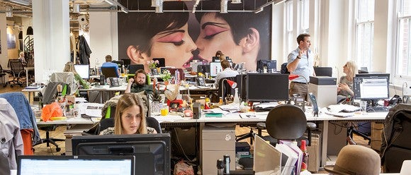 Omnicom office with several workers at their computers and makeup advertisement prominently displayed on a back wall