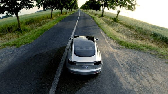 A silver Model 3 driving on an open country road with trees and greenery on both sides
