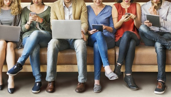 People use laptiops, phones, and tablets sitting in a row.