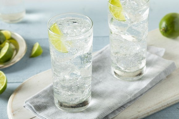 Two glasses of sparkling water with lime wedges sit on a cloth napkin.