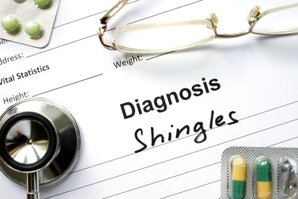 A piece of paper with the words Diagnosis and Shingles on it and medication, stethoscope, and glasses on top.