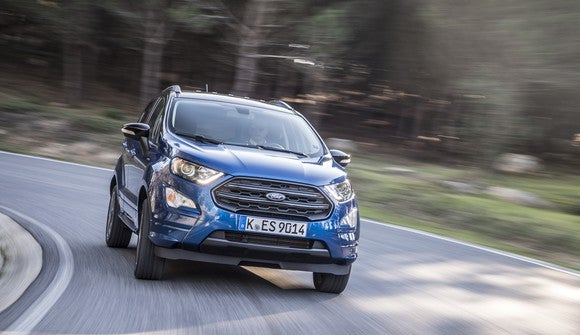 A blue 2018 Ford Ecosport, a small SUV, on a curvy road.