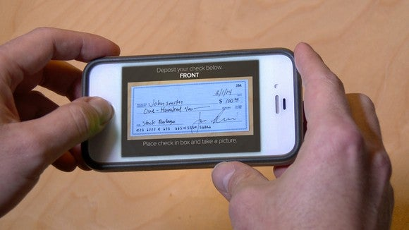 A person using a mobile phone to deposit a check into his bank account.