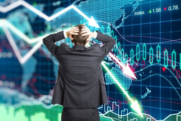 A man in a gray suit holding his head with his hands as he looks at a slumping stock chart.