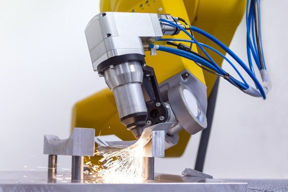 Laser on robotic arm cutting metal.