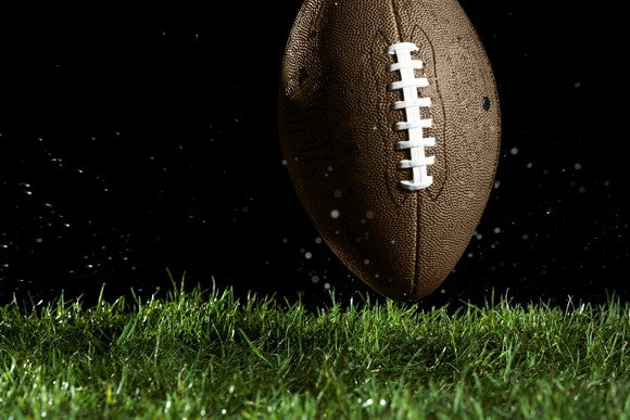 A football on turf, black background.