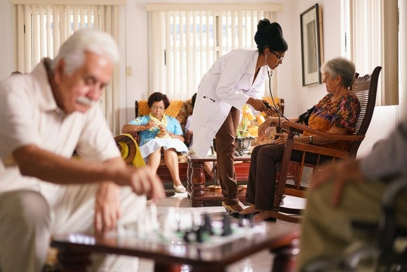 A doctor tends to an older woman inside an assisted living facility, as a game of chess is being played in the foreground