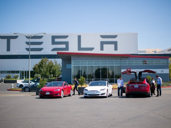 Tesla vehicles and people outside Tesla's factory.