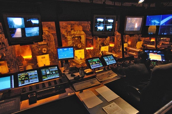 Control room facility with about a dozen monitors, looking out at a steel production factory floor.