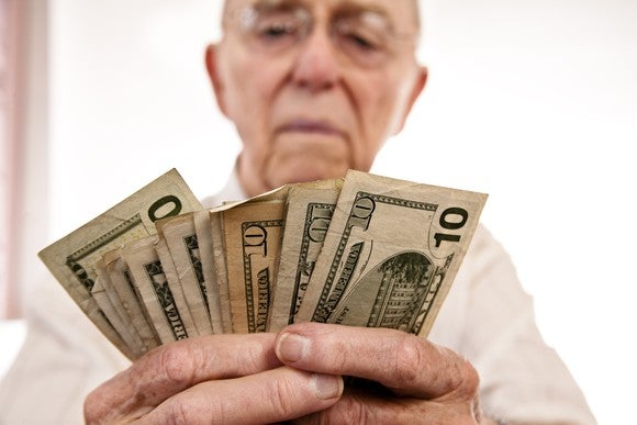 An elderly man looking at fanned-out $1 and $10 bills he's holding with both hands.