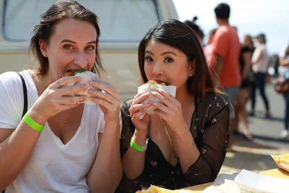 Two young women eating Shake Shack burgers at a new location opening.