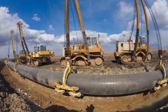 Wide shot of cranes installing an oil pipeline