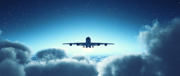 Airplane flying above the clouds with a starry sky behind it