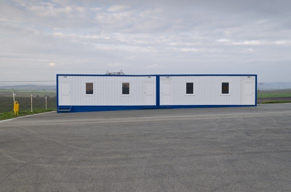 Modular building with four windows in a parking lot.