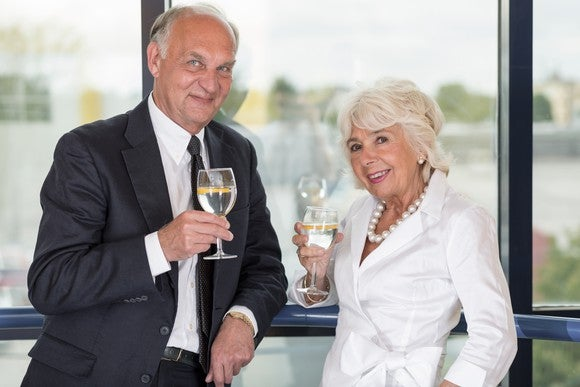 Well-dressed senior couple with wine in their hands, standing in front of a window.