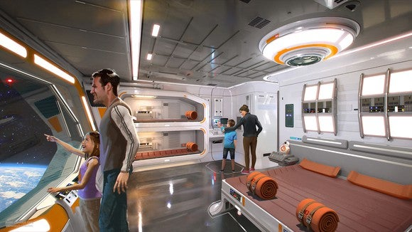 A Star Wars as a spaceship hotel with a man and a girl looking out a big window and a woman and a boy walking around a big bed in the middle with orange blankets and pillows and a bunk bed on the side in the same colors.
