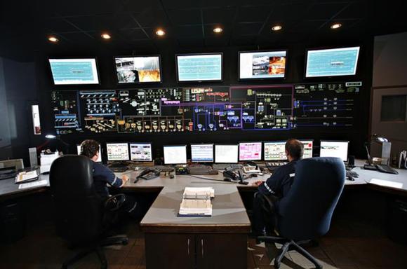Workers sit behind large computer terminals.