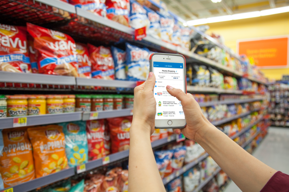 A person uses the new Wal-Mart app in a store, holding their phone up in front of racks of food for sale..