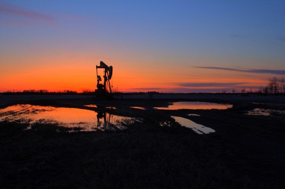 Pumpjack backlit by the setting sun.