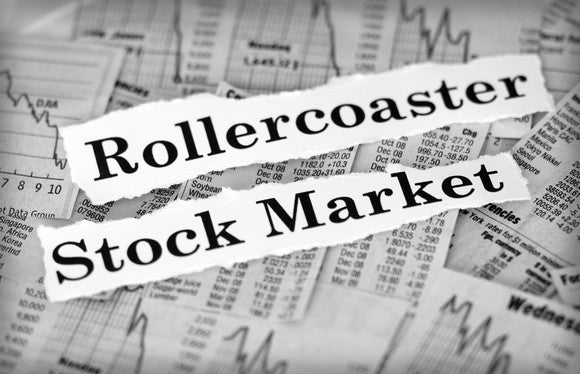 Pieces of paper with rollercoaster and stock market printed on them placed on top of newspaper stock charts and information
