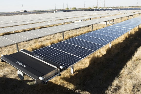 Utility scale solar farm with a robotic cleaner on the first row of panels.