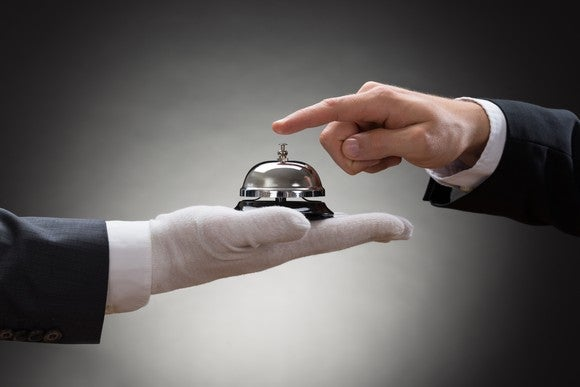 Close-up of a person's hand ringing service bell held by gloved hand