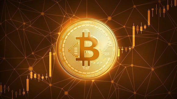 Bitcoin token in front of a rising candlestick chart.