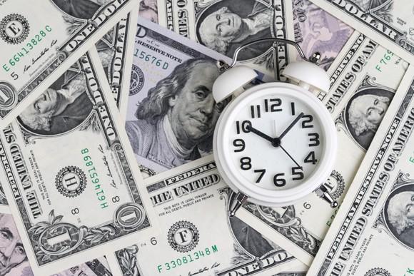 Alarm clock on pile of dollar bills