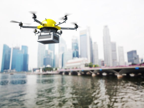 A package-carrying drone flying over a body of water and toward a city.