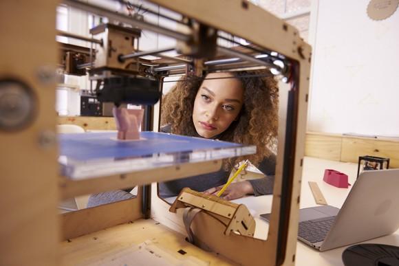 Woman looking at 3D printer.