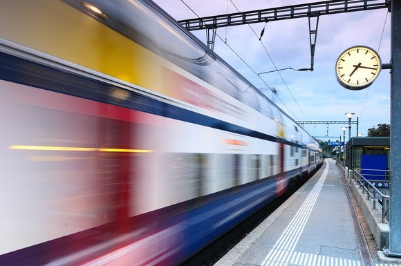 A transit train in motion at a station.