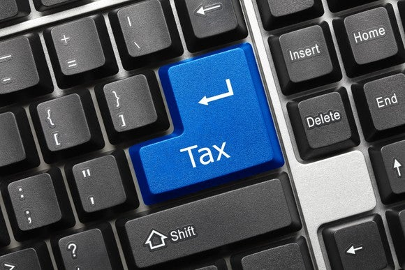 A black keyboard with a big blue key that says tax