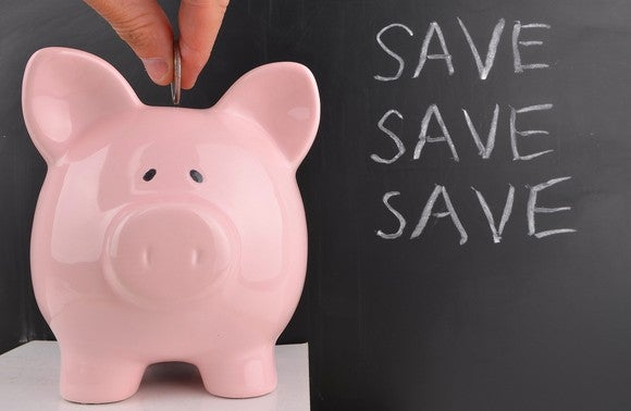 A coin being dropped into a pink piggy bank with the words save save save on a chalkboard behind it