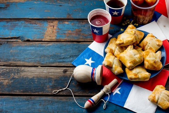 Food and beverage containers depicting the Chilean flag on a picnic table.