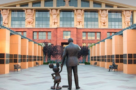 A bronze statue of Walt Disney holding hands with Mickey Mouse.