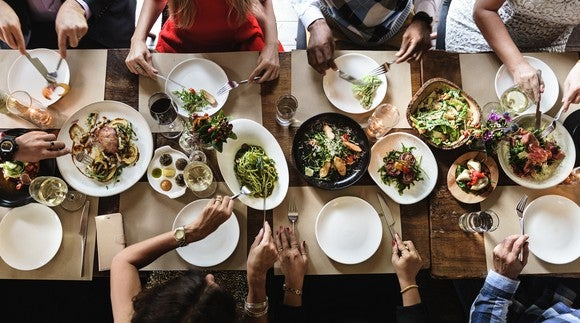 Overhead shot of eight people eating gourmet food at a table.