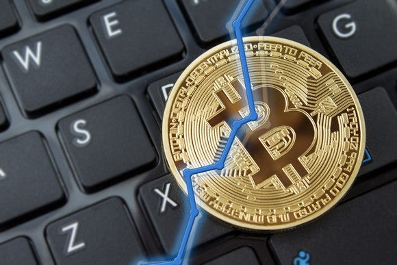 A rising blue line overlaid on a physical gold bitcoin, with a black keyboard in the background.