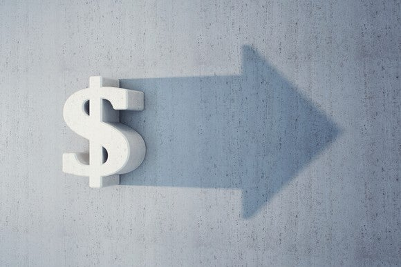 A dollar sign casting a shadow in the shape of an arrow pointing forward.