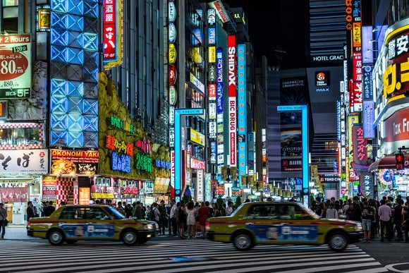 Two yellow Japanese taxis at nighttime, with buildings brightly lit in the background