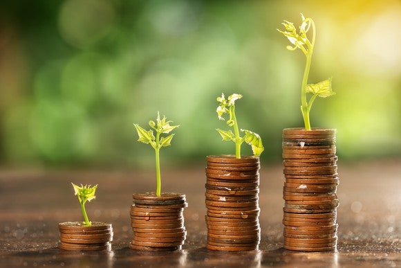 Rising stacks of coins with growing plants on each one.
